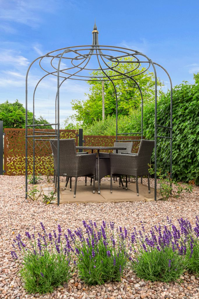 Seating area with rose arch and lavender bed Hampshire